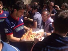 Il calciatore del Bari Sciaudone mentre distribuisce cornetti ai tifosi in fila per il biglietto