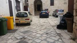 Così si presenta l'atrio da cui si accede al Castello di Conversano: auto parcheggiate e raccoglitori di rifiuti
