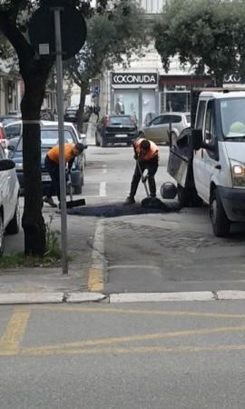 Operai mentre lavorano con l'asfalto per la copertura dei crateri in Piazza Carmine